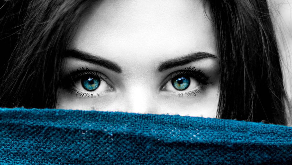Frauengesicht hinter einem blauen Tuch