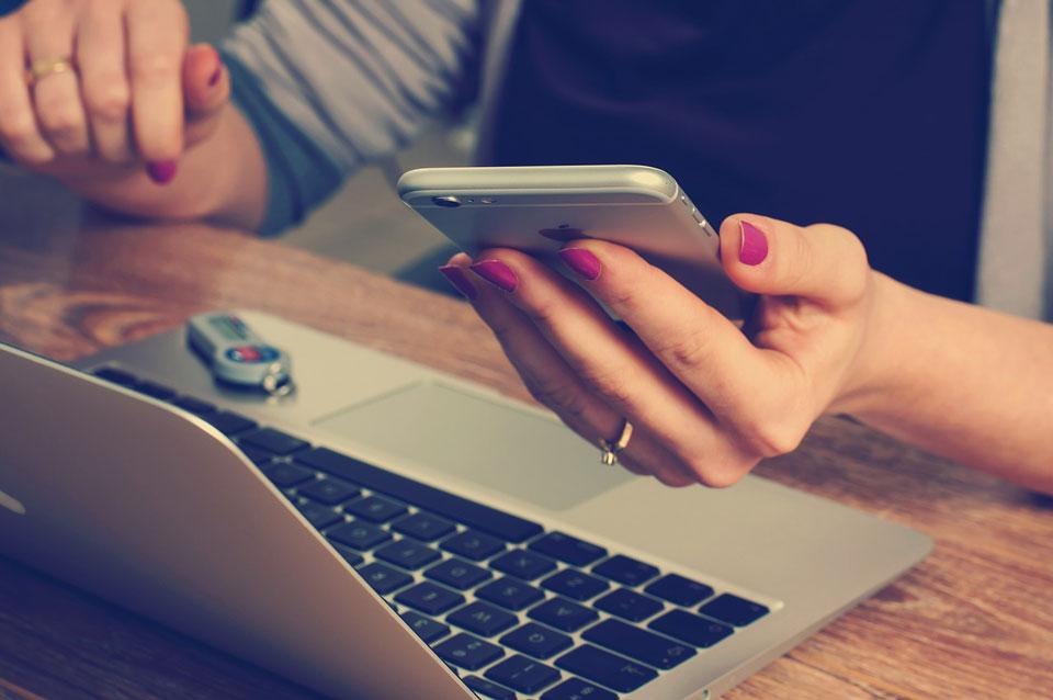 Eine Frau nutzt Laptop und Smartphone für die Zusammenarbeit im Unternehmen