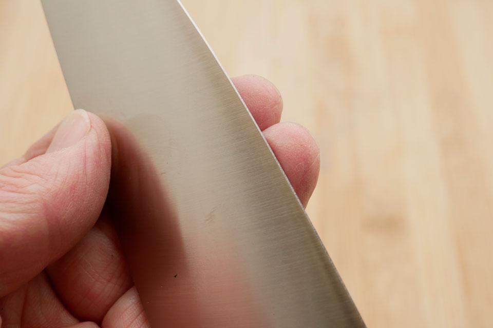 Mit der Hand fühlen, ob noch Grat an der Messerklinge ist