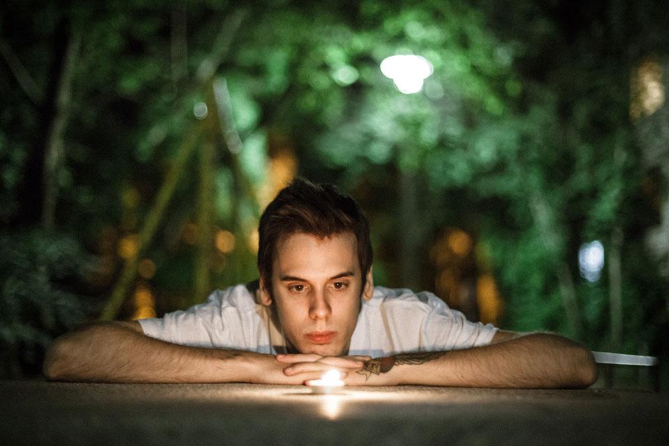 Ein junger Mann schaut einer Flamme beim brennen zu.