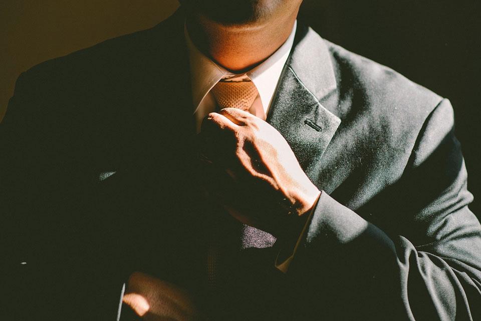 """Der innere Antreiber """"Sei perfekt"""" kann zu Stress führen. Mann im Anzug bindet sich die Krawatte."""