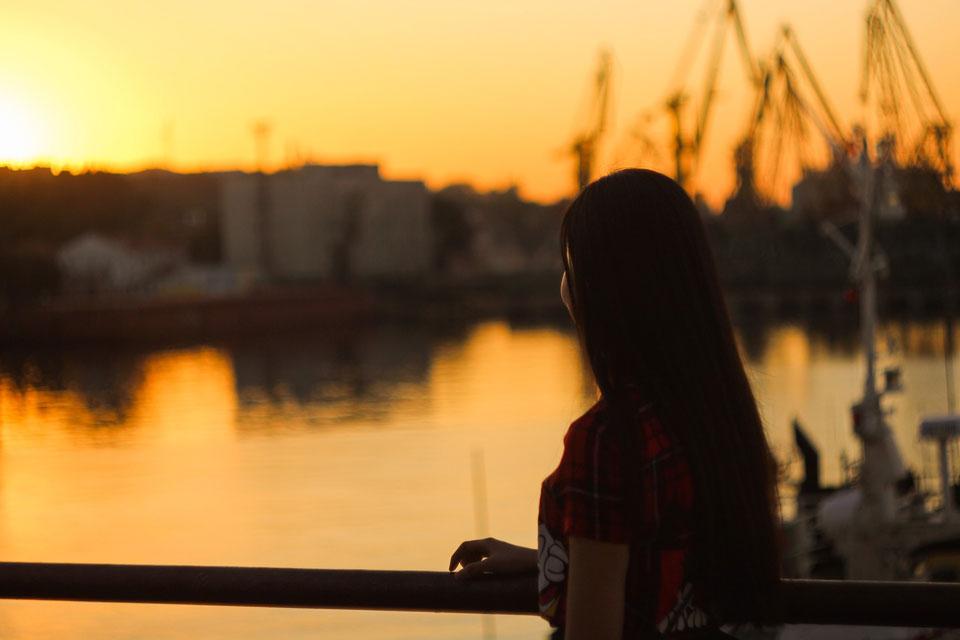 Eine junge Frau beobachtet den Sonnenuntergang