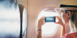 Eine junge Frau macht aus dem Flugzeugfenster ein Foto für die sozialen Netzwerke