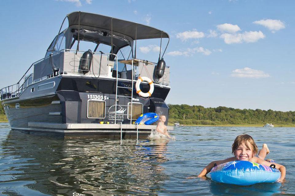 Ein Kind schwimmt neben dem Hausboot