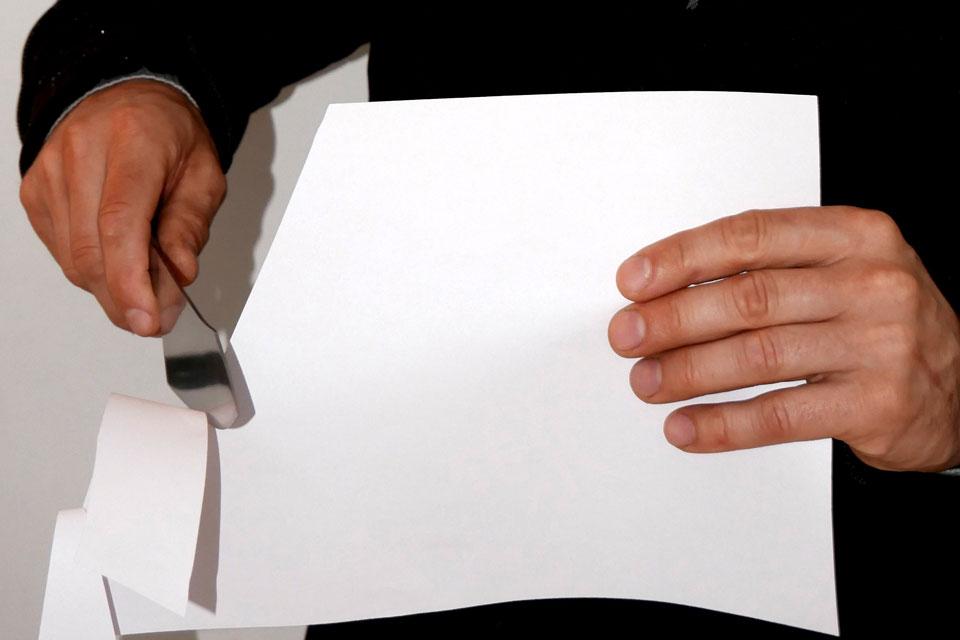 Mit einem Druckerpapier wird die Schärfe des Messers getestet