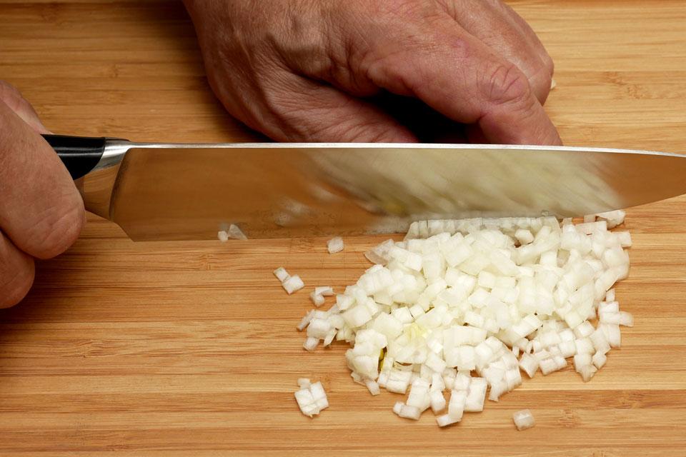 Mit scharfem Messer Zwiebeln schneiden