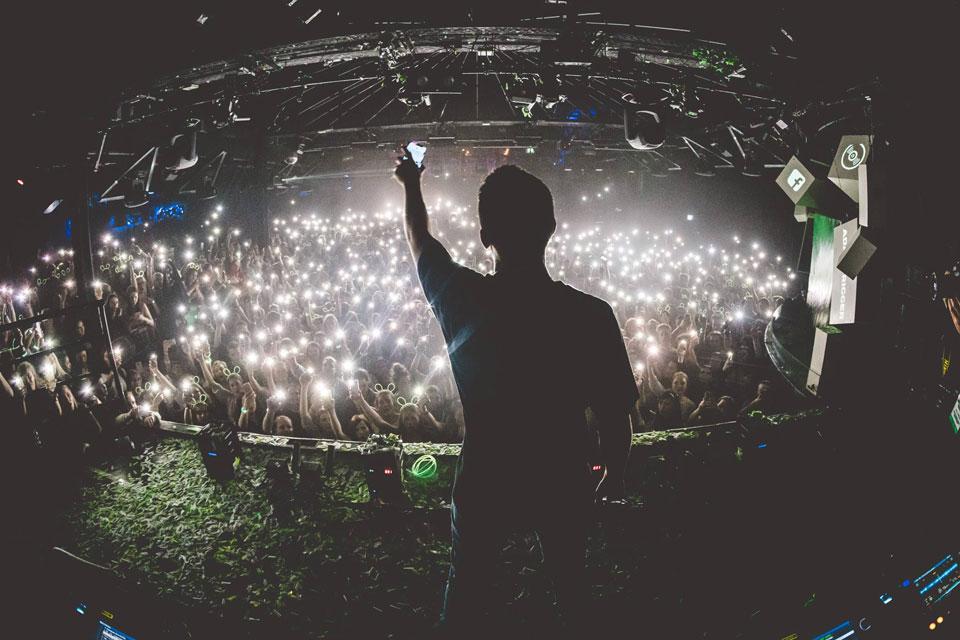 Ein Jugendlicher steht auf der Bühne und streckt sein Smartphone in die Höhe