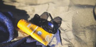 Badetuch mit Sonnenschutz und Sonnenbrille am Strand