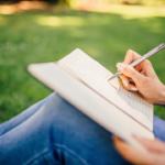 Eine Frau schreibt im Freien eine Geschichte in ihr Schreibheft
