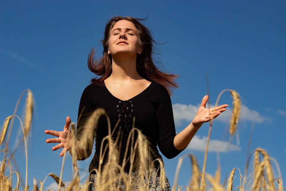 Eine Frau schliesst in einem Feld für ein paar Sekunden die Augen