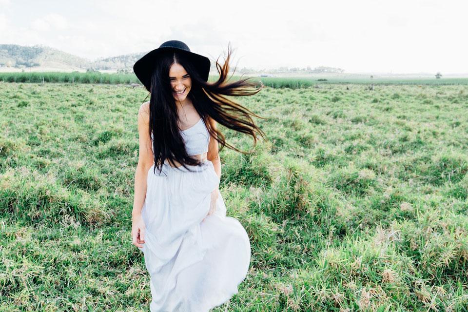 Ein junge Frau in weissem Kleid und schwarzem Hut im grünen Feld
