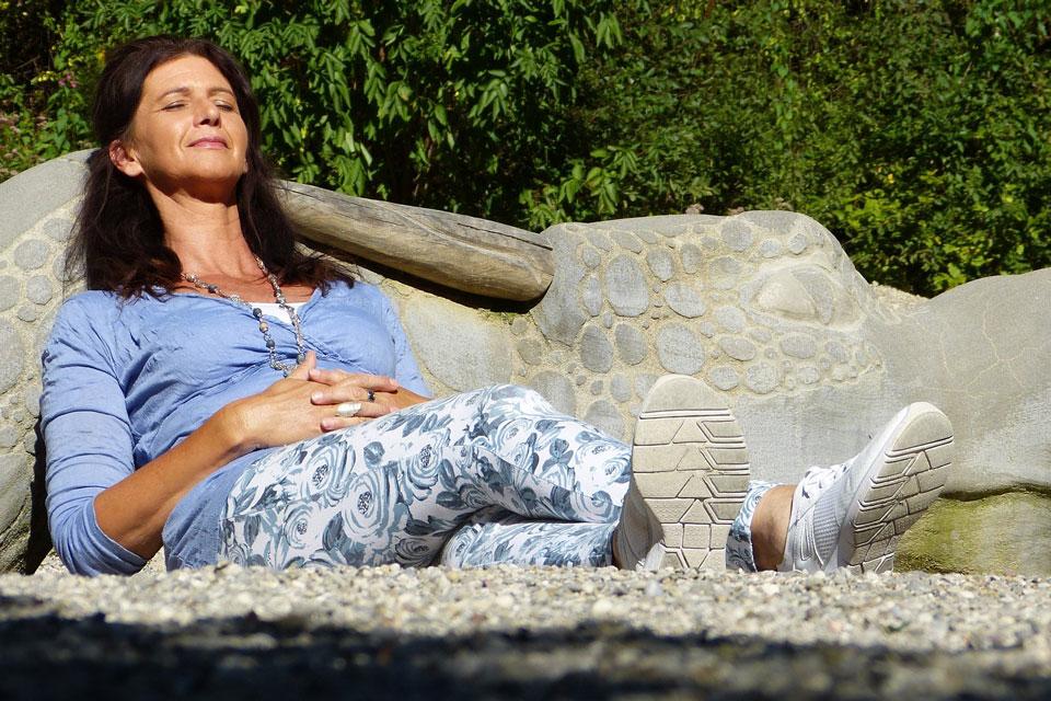 Ein Frau atmet auf einer Steinbank tief durch