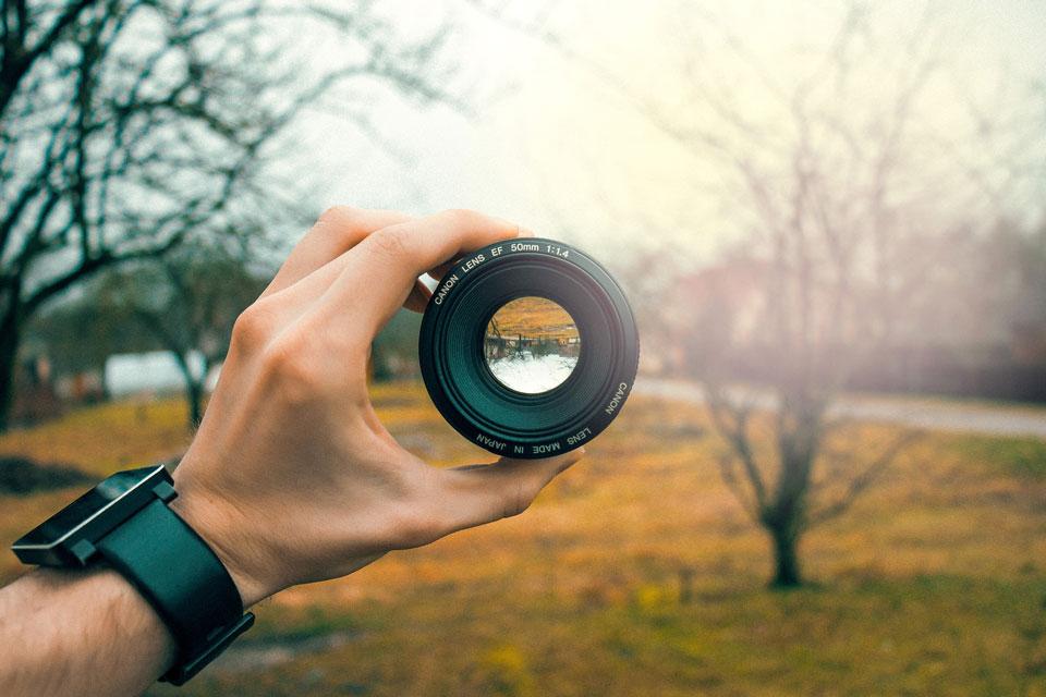 Blick durch ein Foto-Objektiv in einer offenen Landschaft