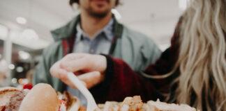 Eine Frau isst mit Heißhunger Fastfood