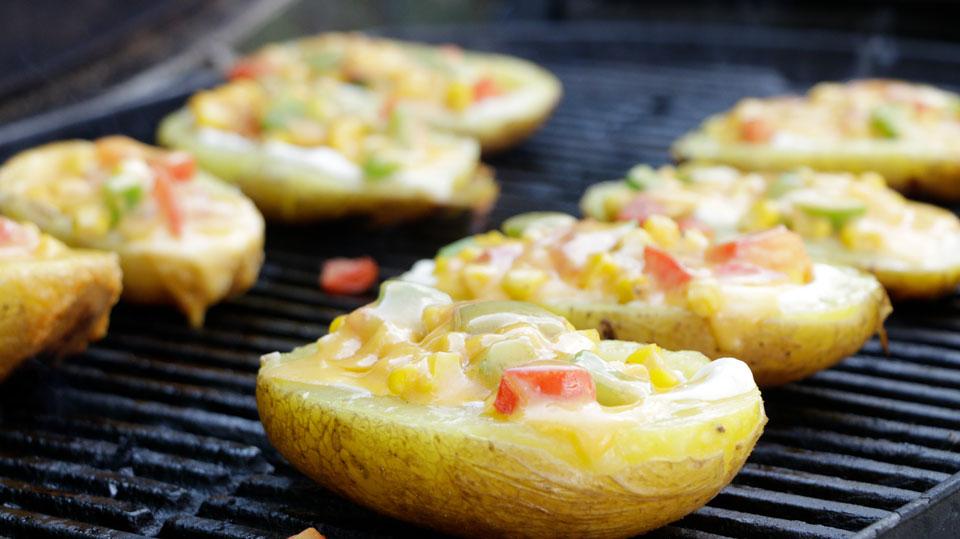 Kartoffelspeisen in Schiffchen-Form werden auf dem Grill gegart