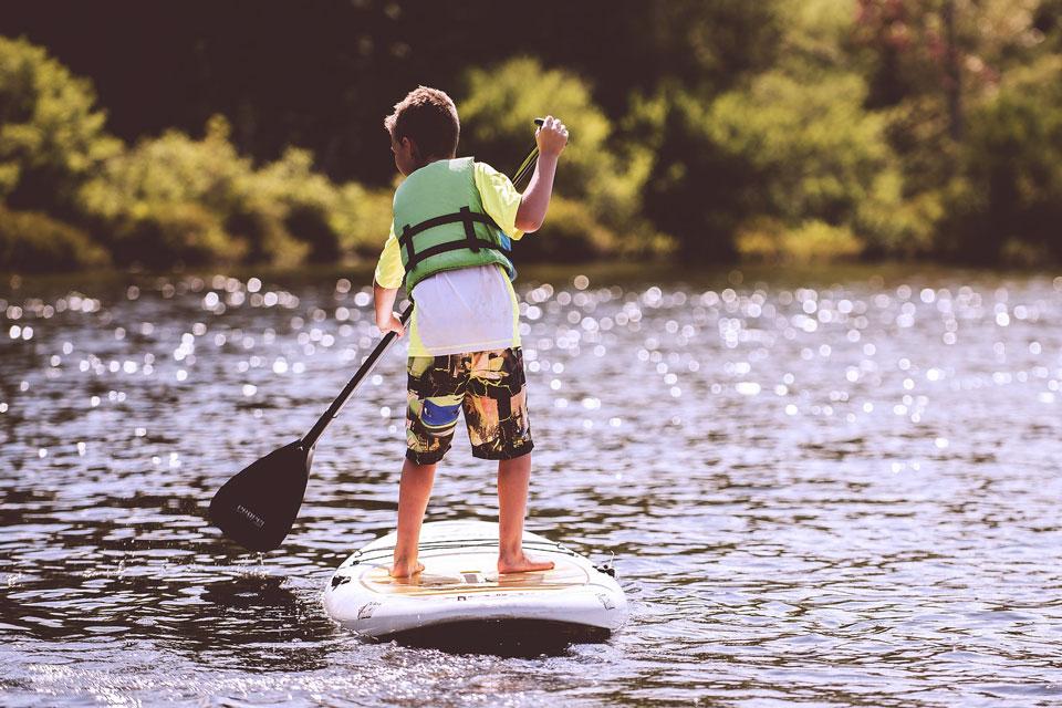 Junge mit Board im Wasser am paddeln