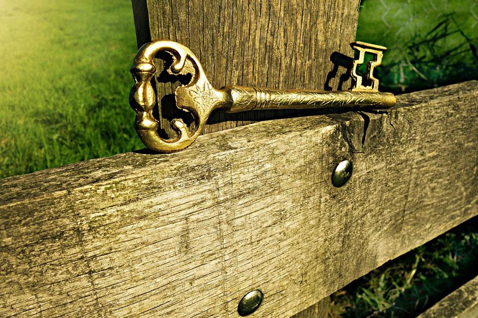 Auf einer Holzbank liegt ein goldener Schlüssel