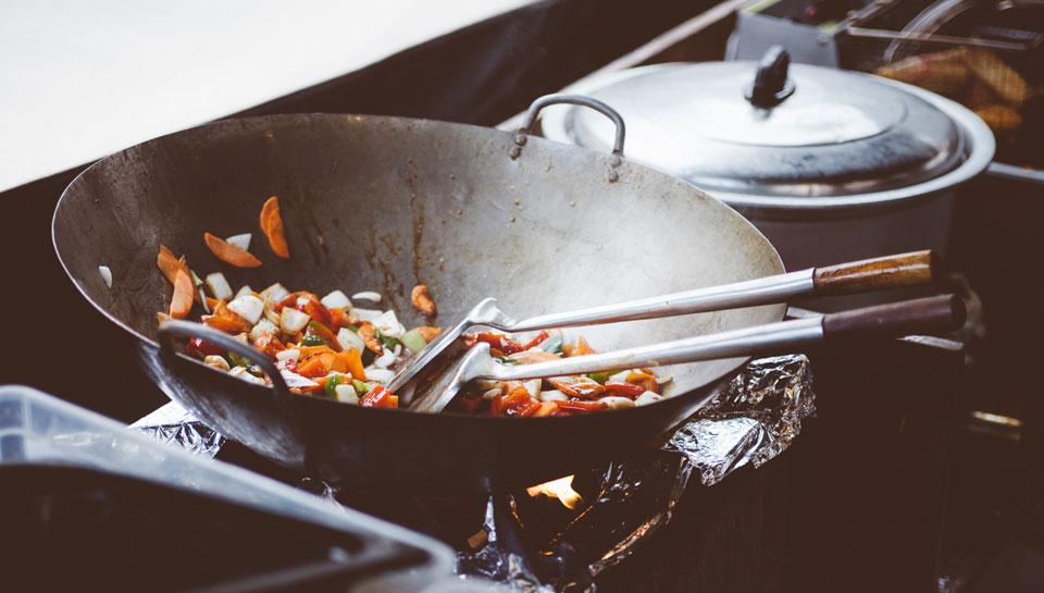In einer Garküche wird Gemüse in einem Wok zubereitet und kann Reisedurchfall auslösen