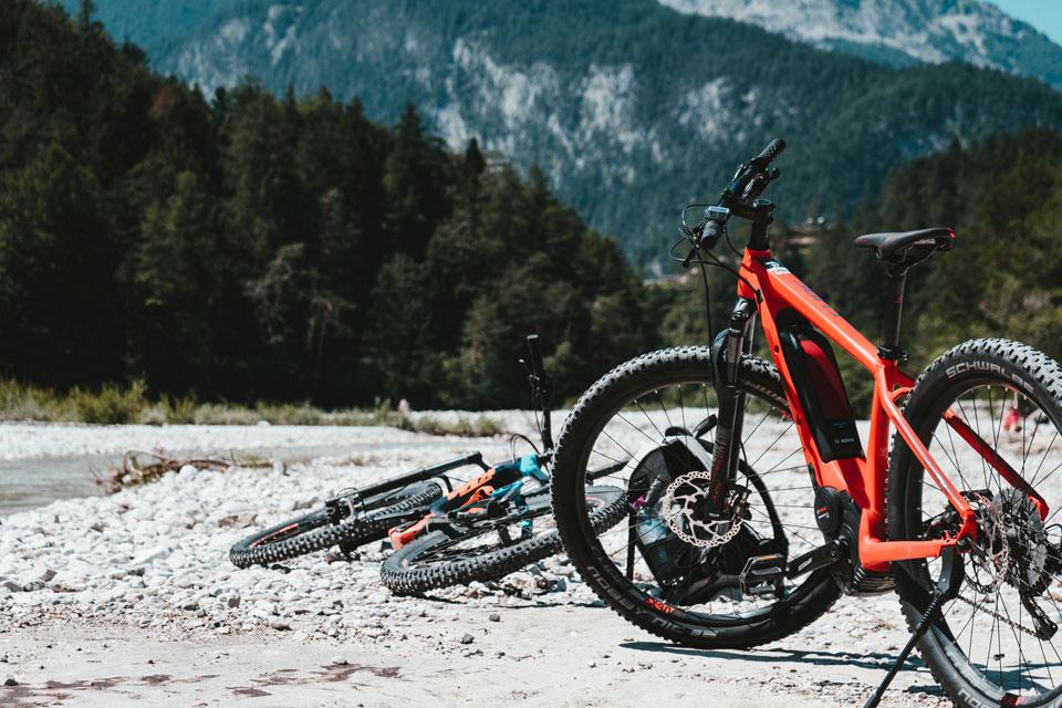 E-Bikes stehen in einem Flussbett in den Bergen