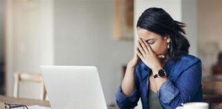 Ein junge Frau am Arbeitsplatz leidet an einer Erkältung