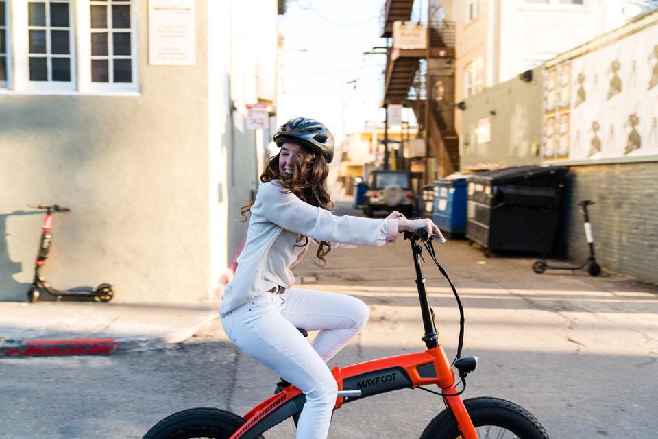 Eine junge Frau fährt mit dem E-Bike zur Arbeit.