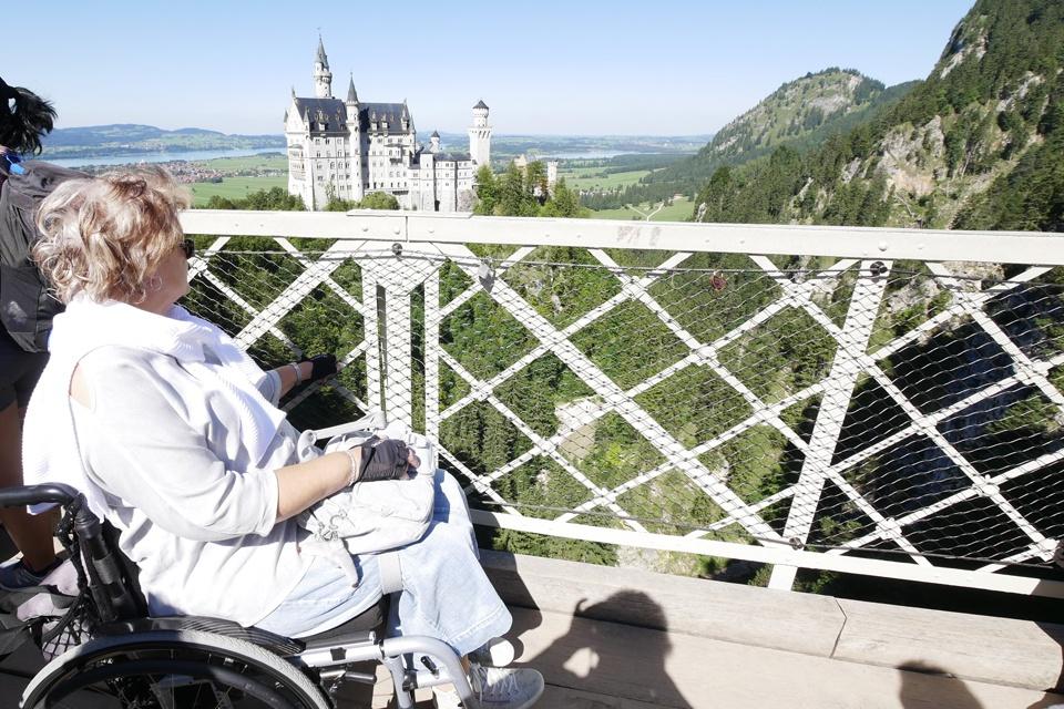 Eine Rollstuhlfahrerin blcikt auf das Schloss Neuschwanstein