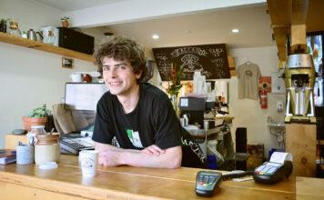 Ein glücklicher Arbeitnehmer steht im Restaurant hinter der Theke
