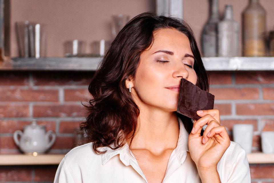 Ein Frau hat Lust auf Schokolade und riecht daran