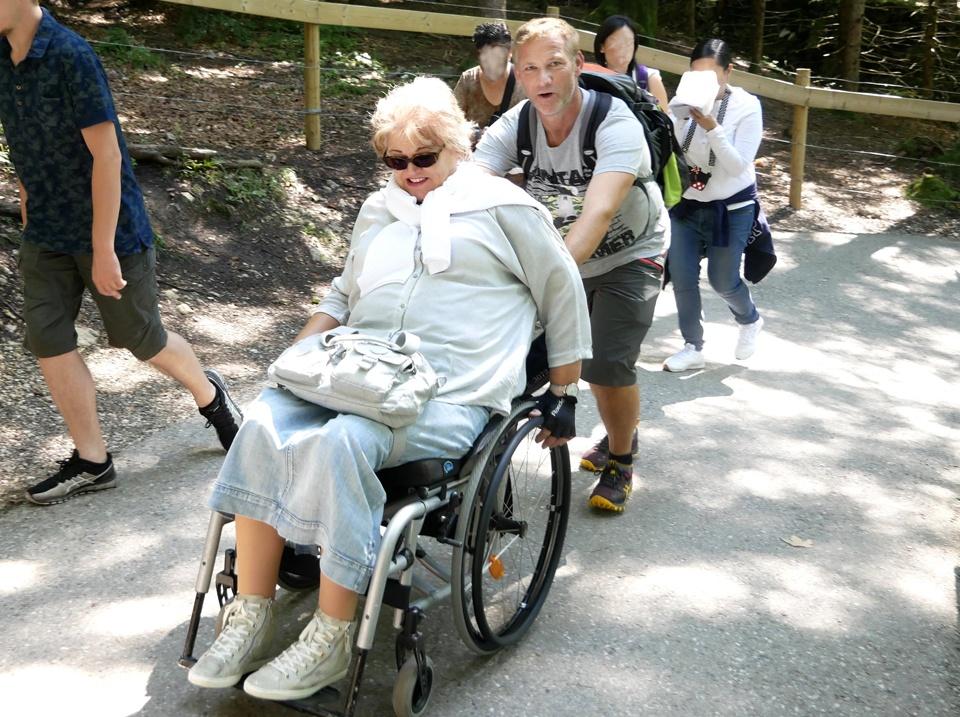Eine Frau im Rollstuhl wird geschoben