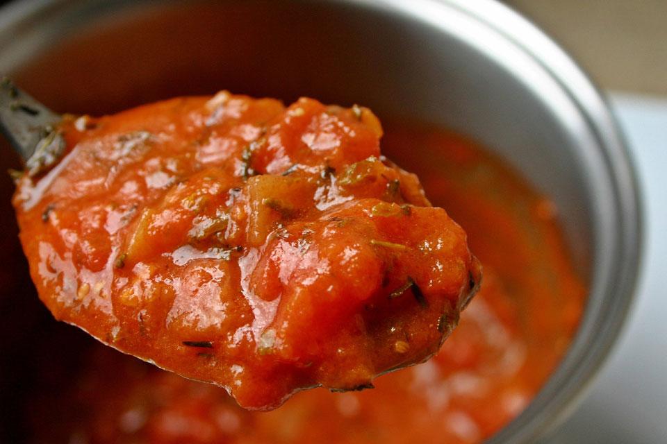 Tomatenfruchtfleisch auf einem Löffel für die perfekte Pizza