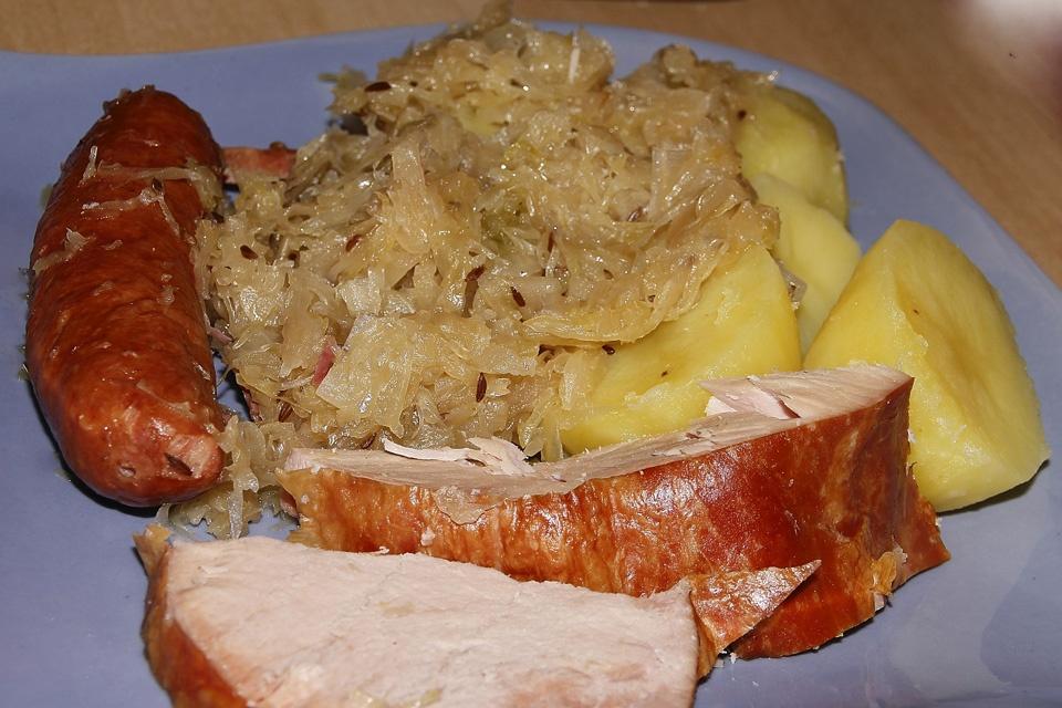 Deftige Hausmannskost mit Speck, Wurst, Sauerkraut und Kartoffeln