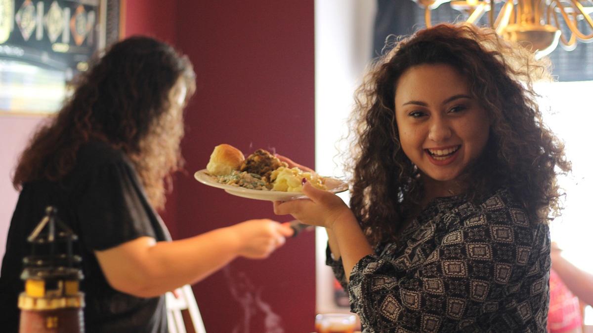 Eine Frau betrachtet ihre Mahlzeit als Glücklichmacher