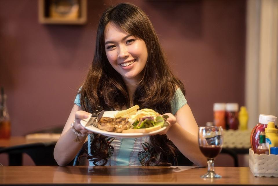 Eine jung Frau erhält glückselig ein Fleischgericht