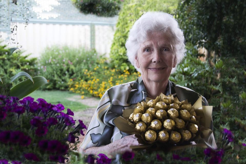 Eine alte Dame bietet Schokokugeln als Glücklichmacher an