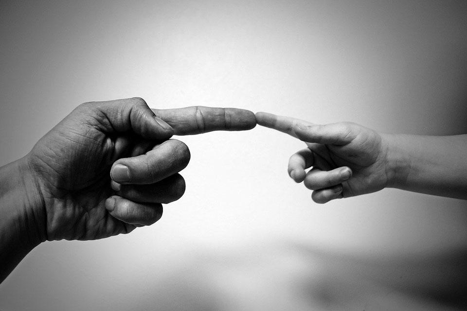 Vater und Kind berühren als Zeichen der Verbundenheit die Zeigefinger