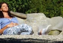 Eine Frau in den Wechseljahren sitzt im Freien