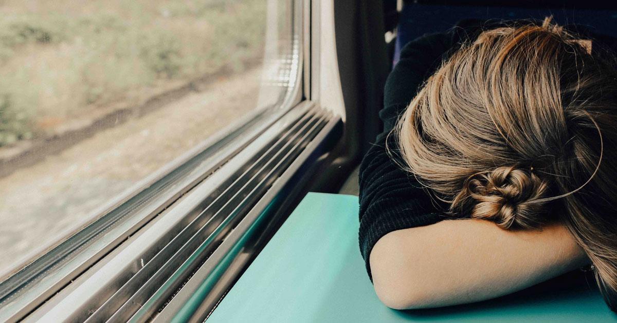 Eine Frau hat Schlafmangel im Zug