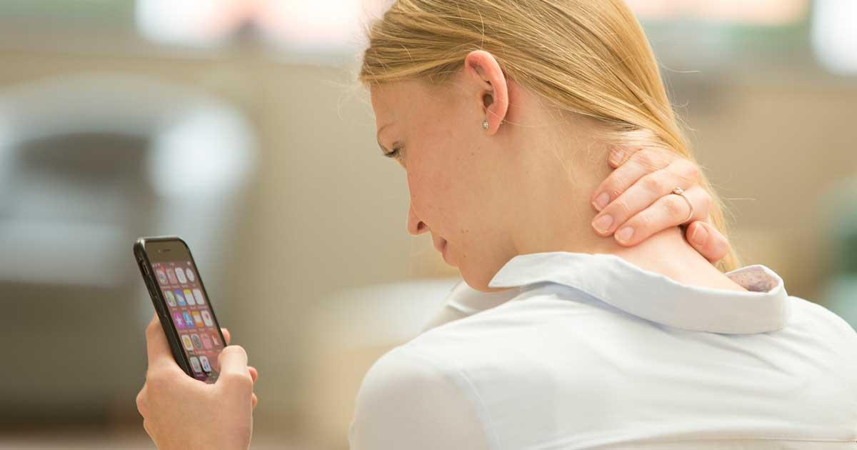 Eine junge Frau hat Nackenschmerzen aufgrund der häufigen Smartphone-Nutzung