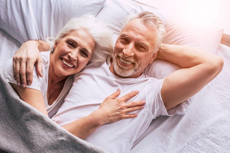 Ein älteres Paar liegt bequem und glücklich in einem ergonomischen Bettsystem