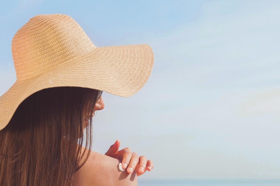 Eine Frau reibt Ihre Haut mit Sonnencreme ein, die neben Sonnenstrahlen auch gegen Viren schützen kann
