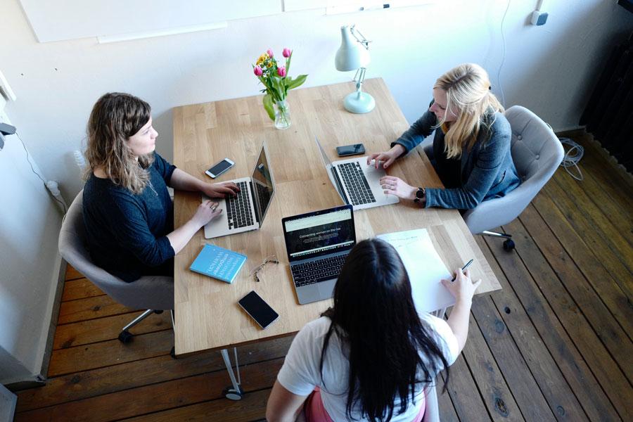 Drei junge Leute sitzen rückenfreundlich am Tisch und arbeiten an ihren Comutern