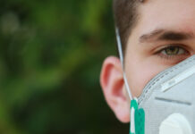 Zum Schutz gegen Viren trägt ein junger Mann einen Mundschutz