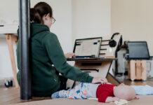 Eine selbstständige Mutter arbeitet am Computer während Baby schläft