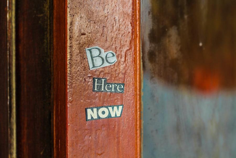Be here now auf einer Holzplatte als Symbol für Achtsamkeit unde Selbsfürsorg