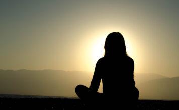 Eine Frau schaut einen Sonnenuntergang und kommt mit Achtsamkeit zur Ruhe