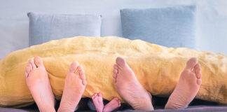 Füsse einer Frau, Kind und Mann unter der Decke als Symbol für aertgerecht schlafen