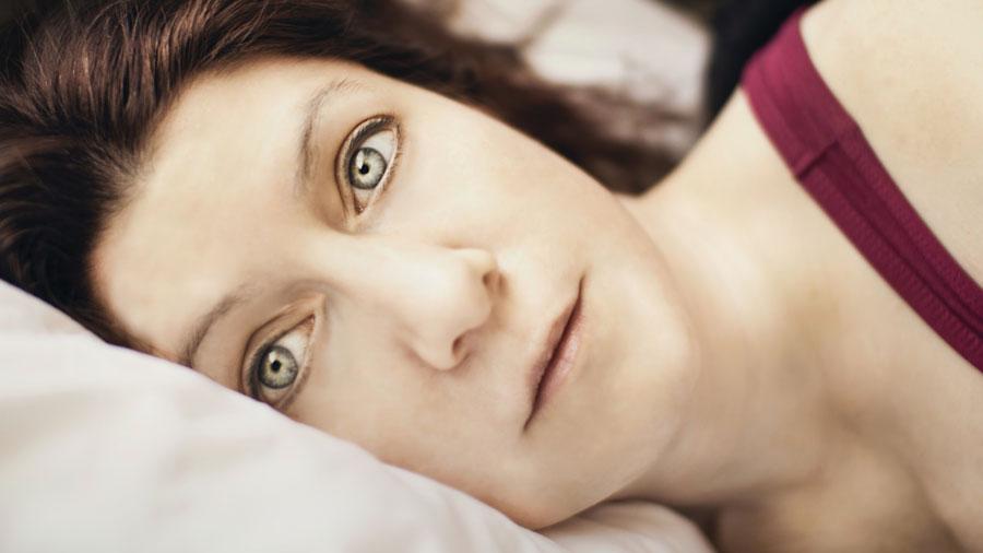 Eine Frau liegt wach im Bett und kann nicht schlafen