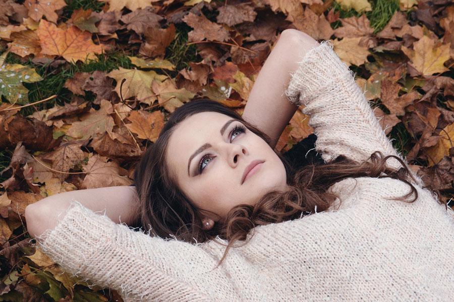 Eine junge Dame liegt auf Laub und denkt nach