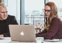 Ein Paar schaut sich am Tisch über den Laptop ein Online Event an und erhält Denkanstöße für ein gesundes Leben und Arbeiten nach dem Lockdown