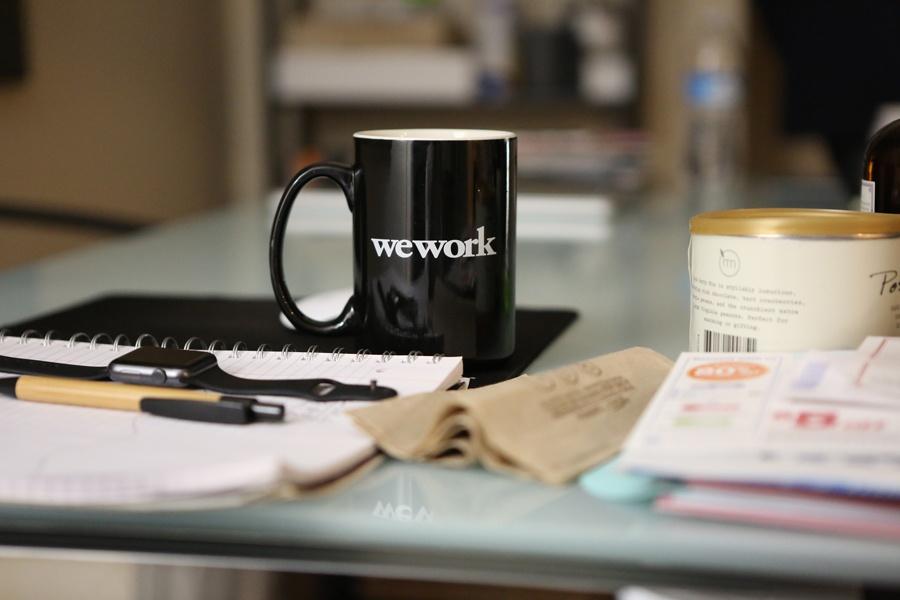Arbeitsplatz im Homeoffice mit Kaffeetasse und Notizbücher